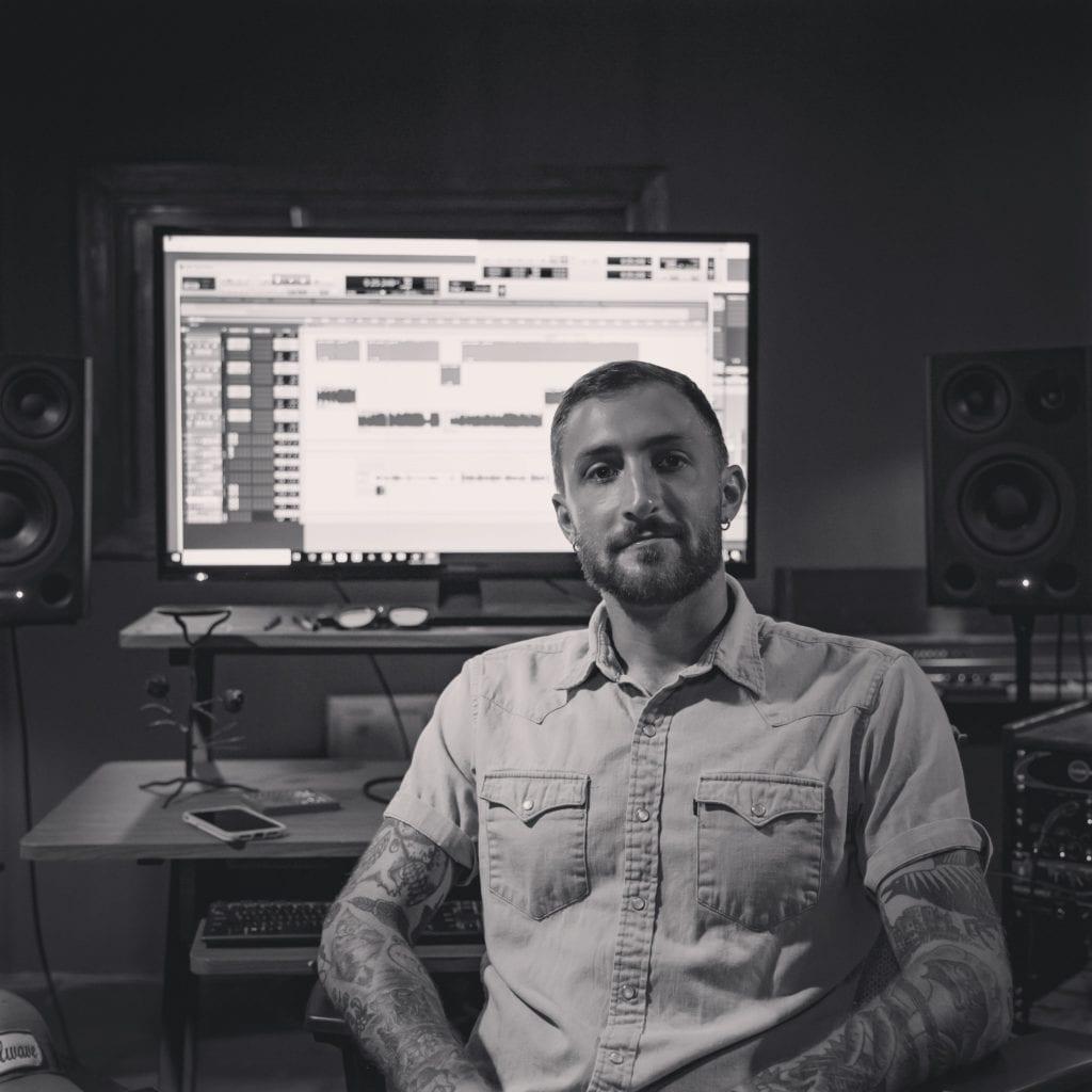 Alex Meylink sitting at the desk in the control room at Stillwave recording studio in Milwaukee